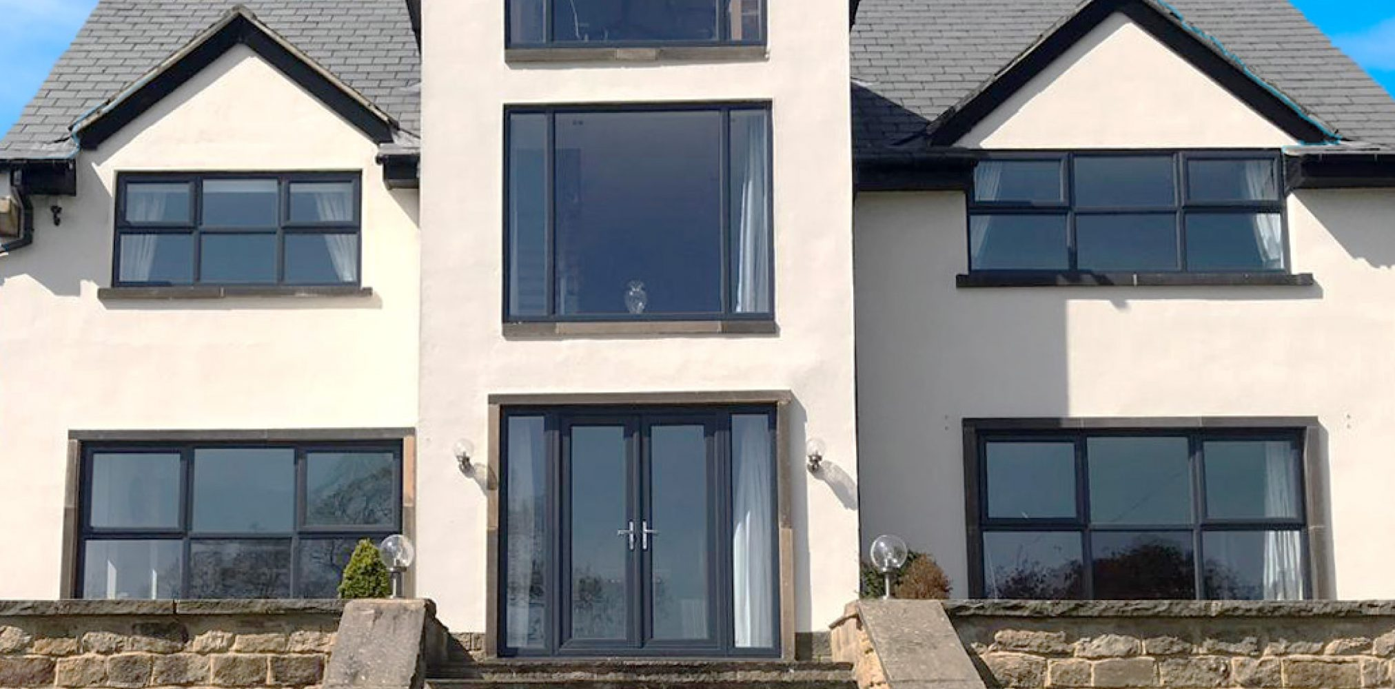 House exterior painted white, uPVC windows and uPVC doors spray painted grey